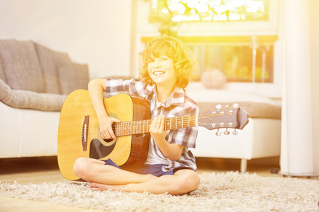 Happy boy singing and playing music with guitar photo