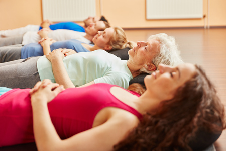 breathing exercise: Group of people with senior relaxing  making breathing exercise at yoga class Stock Photo