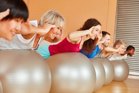 gym ball: Pilates class training their back with gym ball at fitness studio Stock Photo