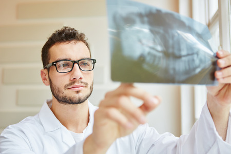 Dentist looking at x-ray image with competence