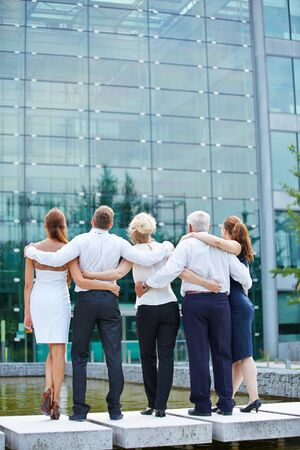 team from behind: Business team from behind embracing and looking to office building Stock Photo