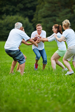 happy senior: Happy family playing american football in the garden
