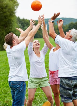 vitality: Happy team playing together with a ball in nature Stock Photo