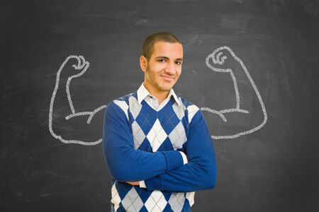 Successful and powerful student with muscles of chalk on blackboard as motivation concept photo