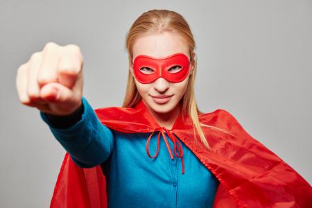 De vrouw kleedde zich als een superheld met gebalde vuist voor carnaval Stockfoto