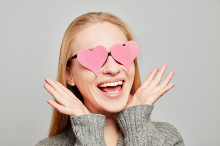 Woman in love with two pink hearts over her eyes Imagens