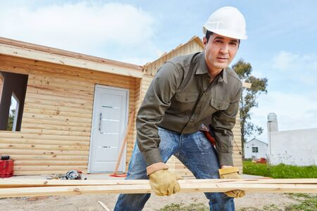 housebuilding: Man as handyman at construction site building woodhouse