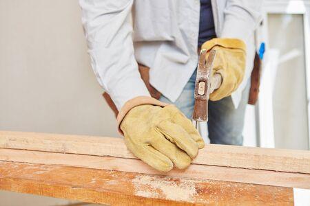 hammering: Carpenter hammering on wood during construction