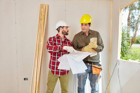construction site: Craftsman and artisan planning with architectural drawing
