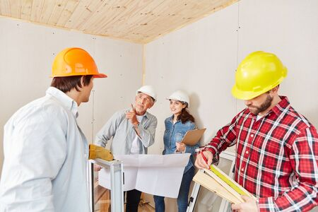 Architect working on house renovation and planning as team with artisans Stock Photo