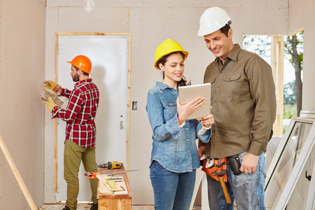 Architects and craftsmen renovating in teamwork at construction site
