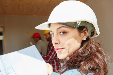 Woman as young architect wearing helmet and planning new building construction