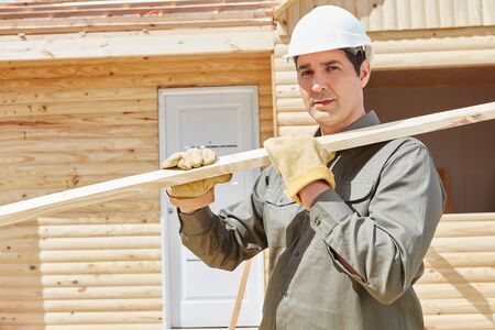housebuilding: Worker carrying wood at construction site during building construction