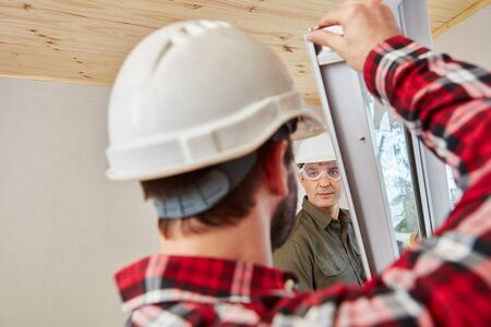 housebuilding: Window fitters mounting window with cooperation