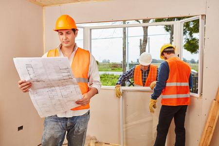 Window fitter team met vloerplan moderniseren nieuw huis