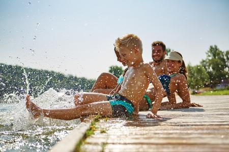 Fam�lia feliz em um lago se divertindo e jogando �gua no ver�o