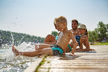 Happy family at a lake having fun and splashing water in summer 版權商用圖片 - 70588460