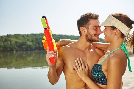 Couple in love hugging at a lake with squirt guns in summer Stock Photo