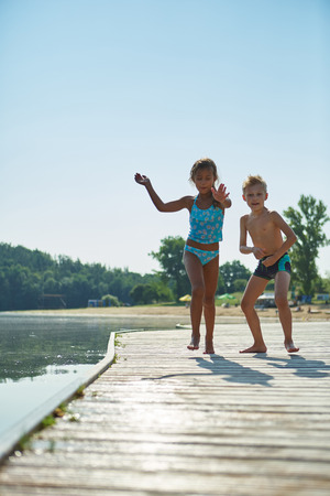 romp: Two children playing on a pier at the lake in summer Stock Photo