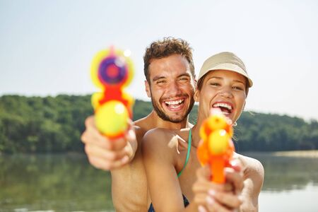 Couple with squirt guns laughing happily in summer Stock Photo