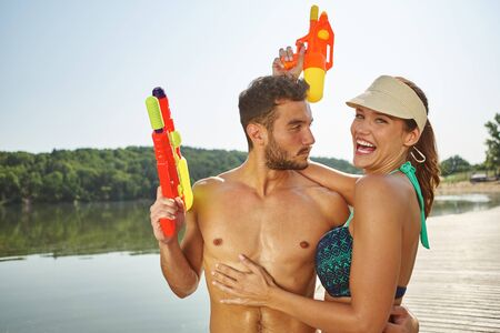 Couple at a lake with squirt guns laughing and having fun on ther holidays