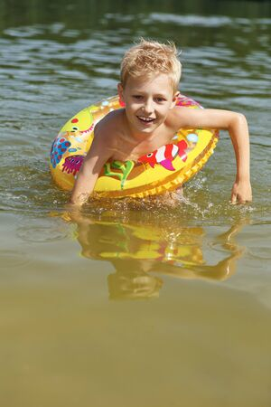Boy learning how to swim with a floating ring in a lake in summer Stock Photo