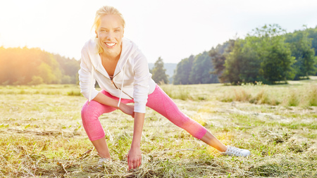 health and fitness: Woman stretching before workout in the park in summer