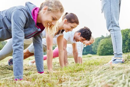 push people: Young people making push ups in training in nature