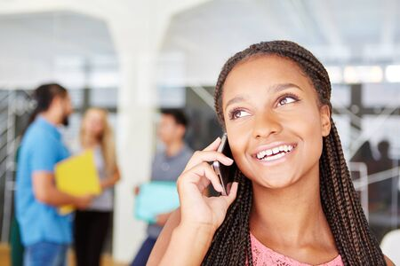 hear business call: African woman calling with smartphone and hears good news