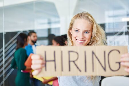 Young woman holding sign reading hiring in start-up