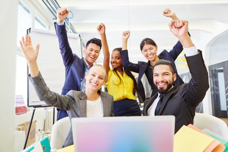 Young business people celebrating in start-up and clenching their fists up in the air