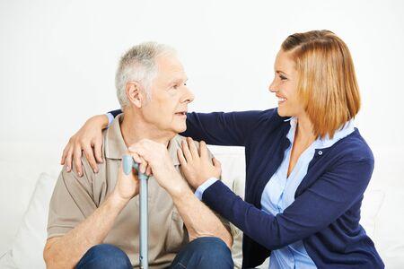 senior adult man: Adult daughter assisting senior man at home Stock Photo