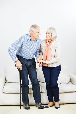 levantandose: Old woman helping senior man getting up from a sofa at home