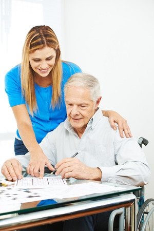 Daughter helping senior father in wheelchair at home solving sudoku puzzles Stock Photo