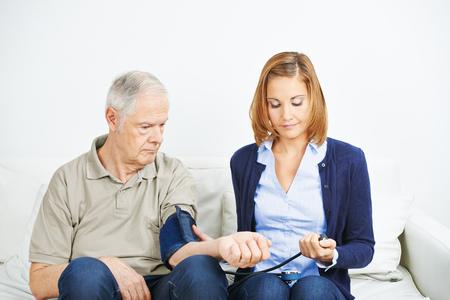 man measurement: Nursing service doing blood pressure measurement for senior man