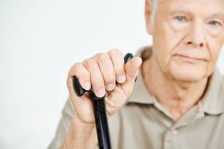 Hand of a pensive senior man with a cane photo