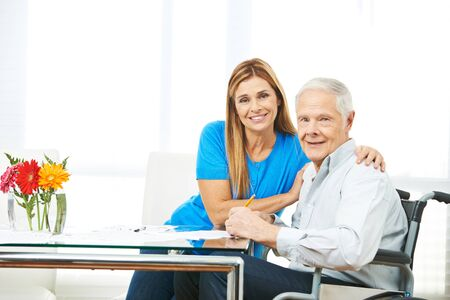 Woman and senior man filling out forms together at home photo