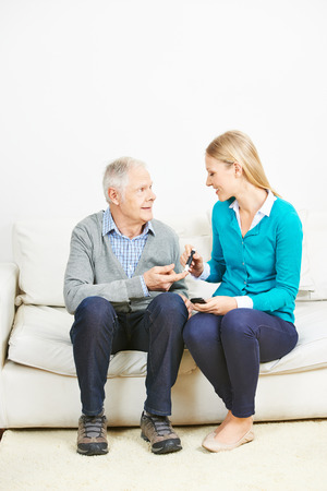 Young woman doing blood glucose monitoring for senior man at home photo