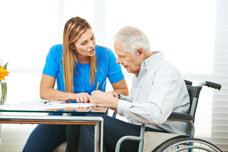 Woman giving consultation to senior man in wheelchair at home