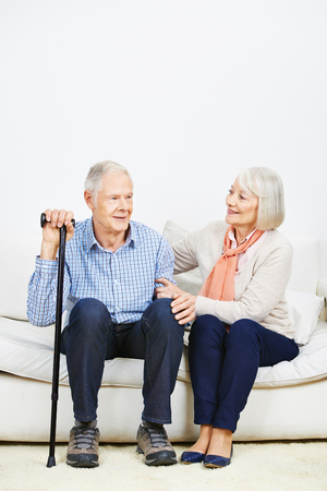 Old woman caring for senior man on a sofa at home photo