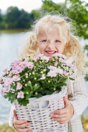 blond girl: Blond girl helping in garden with flowers and plants