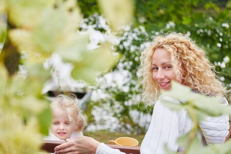 Happy woman and daugther in autumn at garden Stock Photo