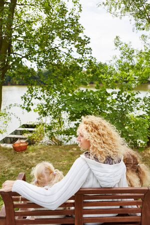 Mother with two kids at lake shore sitting on bench Stock Photo
