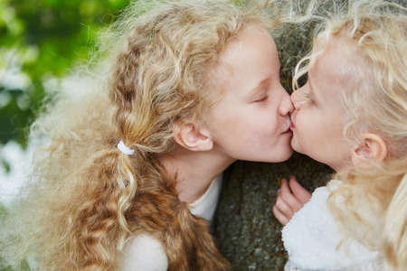 Two little sister girls kissing with sibling love and affection