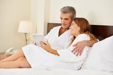 Happy couple streaming videos on tablet computer in a hotel room Stock Photo