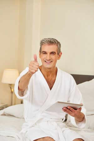 Elderly man with tablet computer holding thumbs up in a hotel room Stock Photo