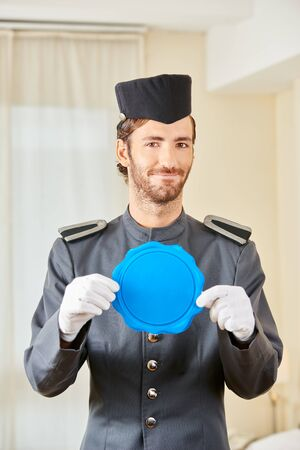 Page in hotel holding blank blue sign in his hands Stock Photo