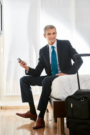 Business man with suitcase and smartphone sitting on bed in a hotel room