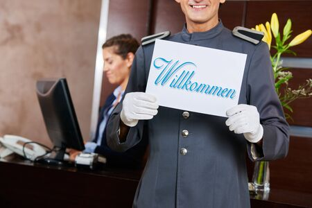 Page at hotel reception holding German sign saying Willkommen (welcome) Stock Photo