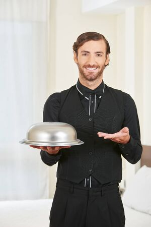 Hotel page serving food with cloche on a tablet in a hotel room Stock Photo